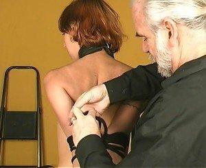 Dude leads tall slim bdsm redhead in dog collar and leash to shackle her